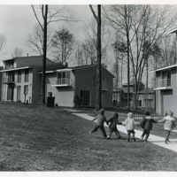Children and dog playing by town<br /> house cluster